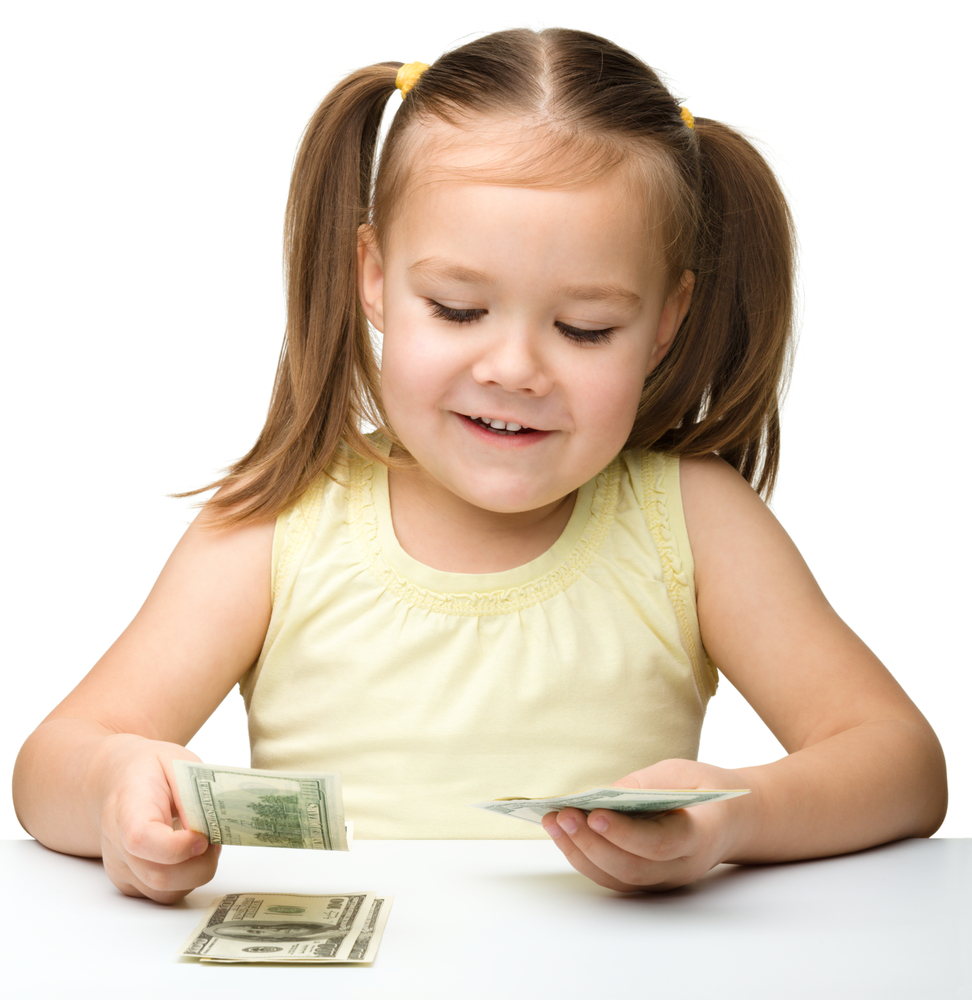 Cute cheerful little girl is counting dollars, isolated over white